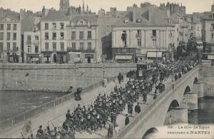 """""""Le 65e de ligne rentrant à Nantes"""" par la rue Bon-Secours. Carte postale timbrée en août 1914"""